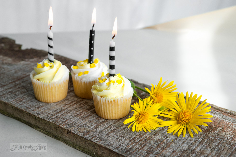Yellow birthday cupcakes on a reclaimed wood plank / FunkyJunkInteriors.net