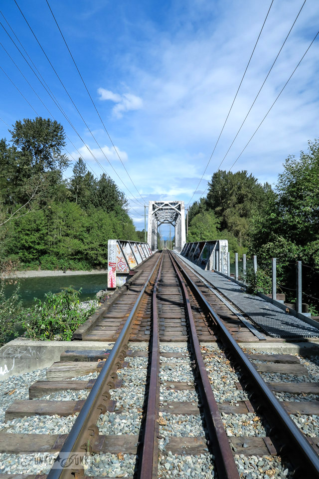 train track bridge over a river with blue sky overhead / funkyjunkinteriors.net