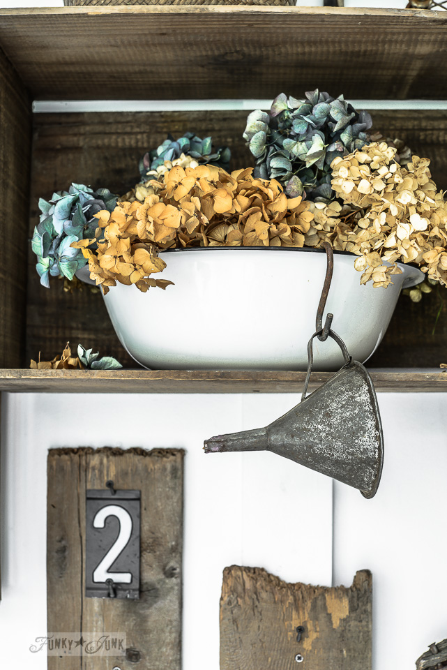 Dried brown and blue hydrangeas inside a crate with a rusty funnel / funkyjunkinteriors.net