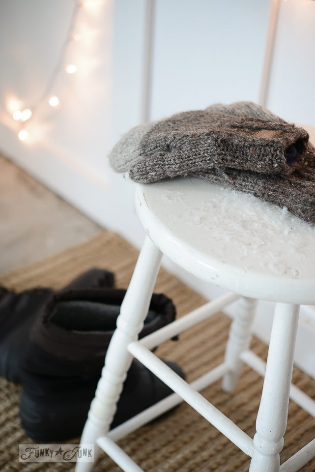winter staging with white stool and mittens in faux snow
