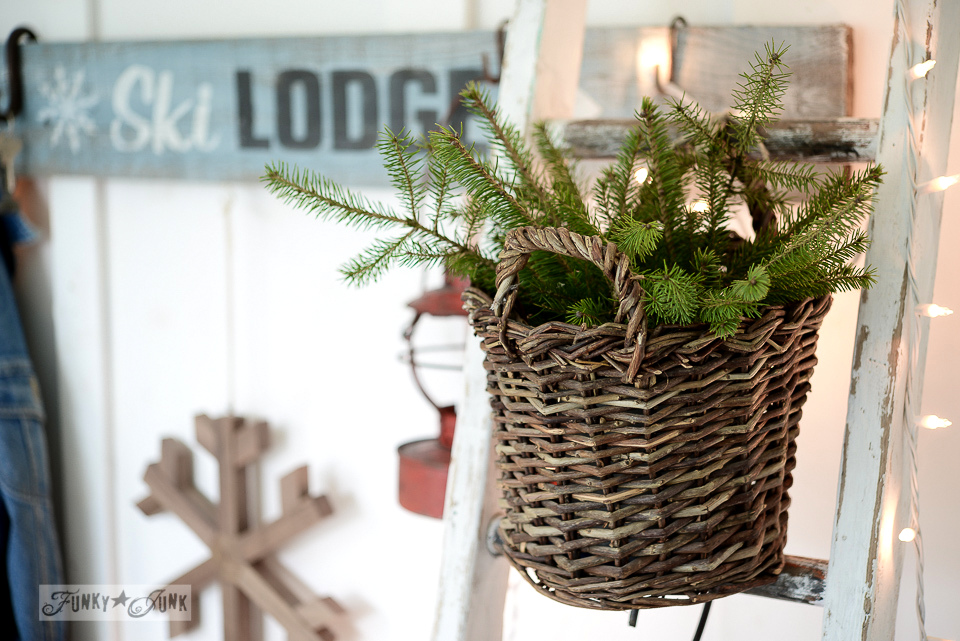 evergreen branches in a wicker basket, hanging on a ladder