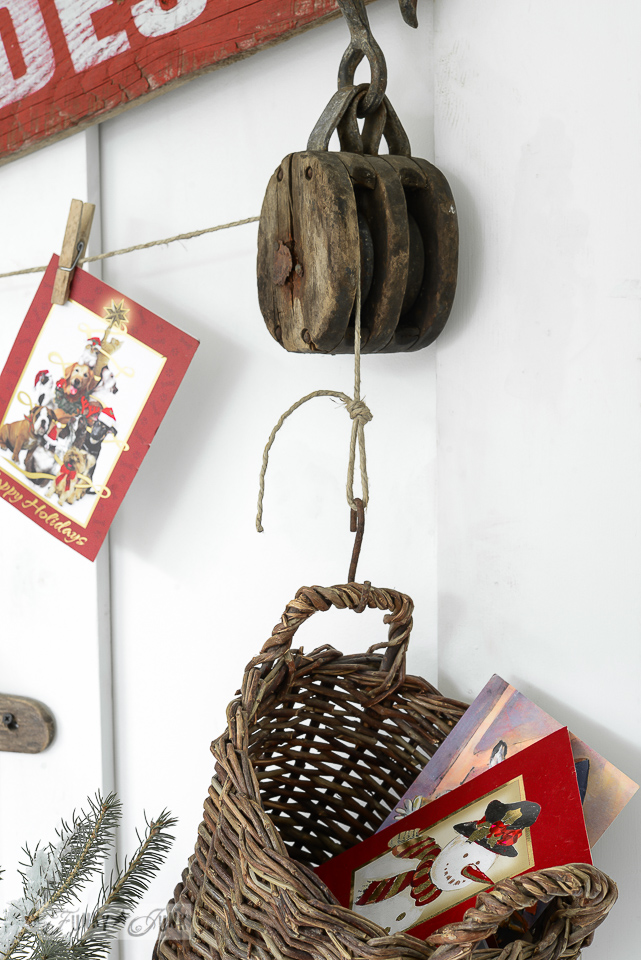 Rustic pulley holding up Christmas cards in a basket from an old Christmas sign / funkyjunkinteriors.net