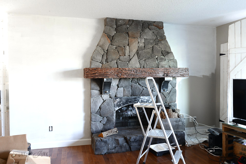 white walls in a living room with a grey rock floor to ceiling fireplace / funkyjunkinteriors.net