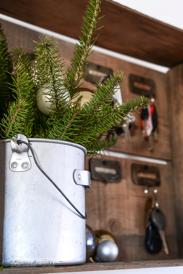 small bucket of evergreen branches for Christmas inside a crate holding keys / funkyjunkinteriors.net