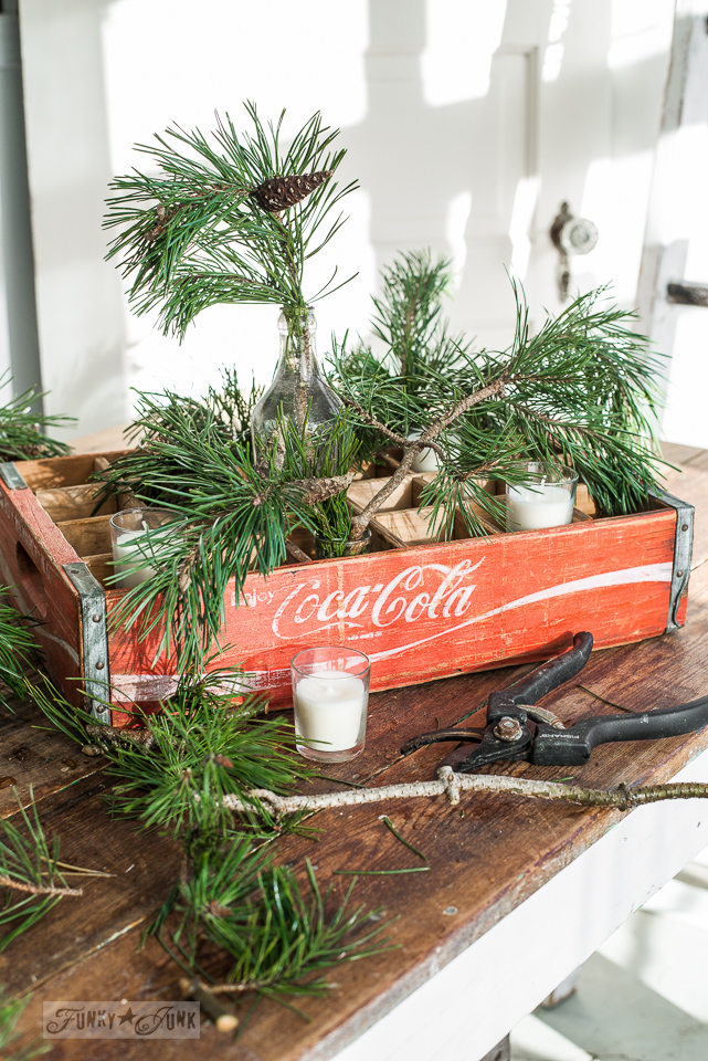 adding greenery to a vintage coke crate for a Christmas candle centrepiece / funkyjunkinteriors.net