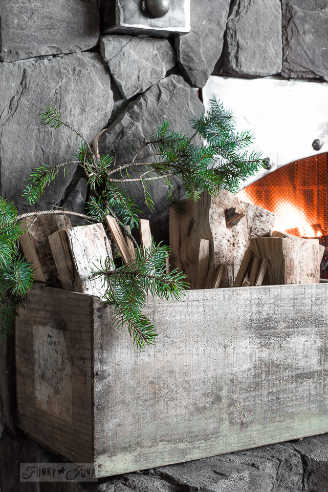 firewood and evergreen branches in a crate for a Christmas mantel / funkyjunkinteriors.net
