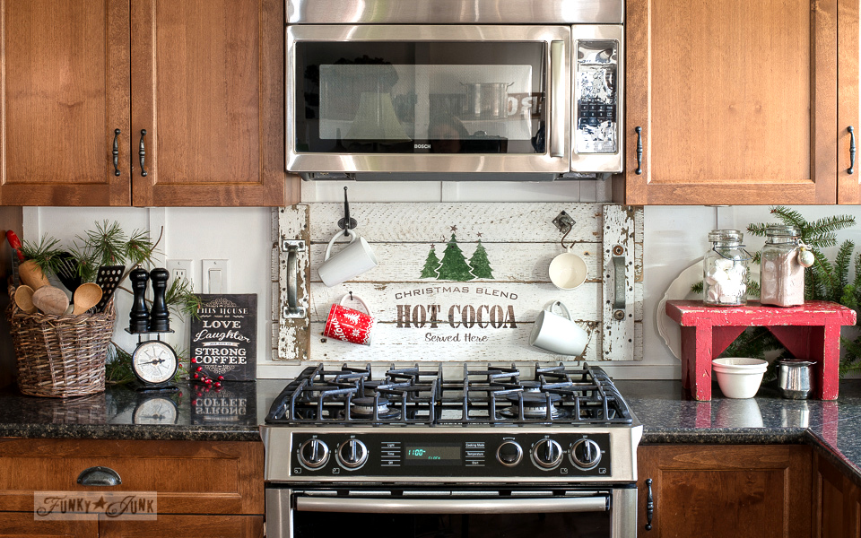 christmas decor in the kitchen with a hot cocoa tray sign and evergreen branches