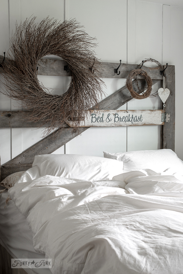 Old horse gate headboard in a master bedroom with wreaths and a Bed & Breakfast sign / www.funkyjunkinteriors.net