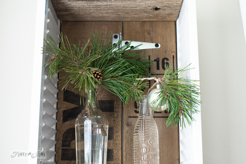 Clear sodapop bottles with evergreen branches in an old shutter shelf for Christmas decorating / www.funkyjunkinteriors.net