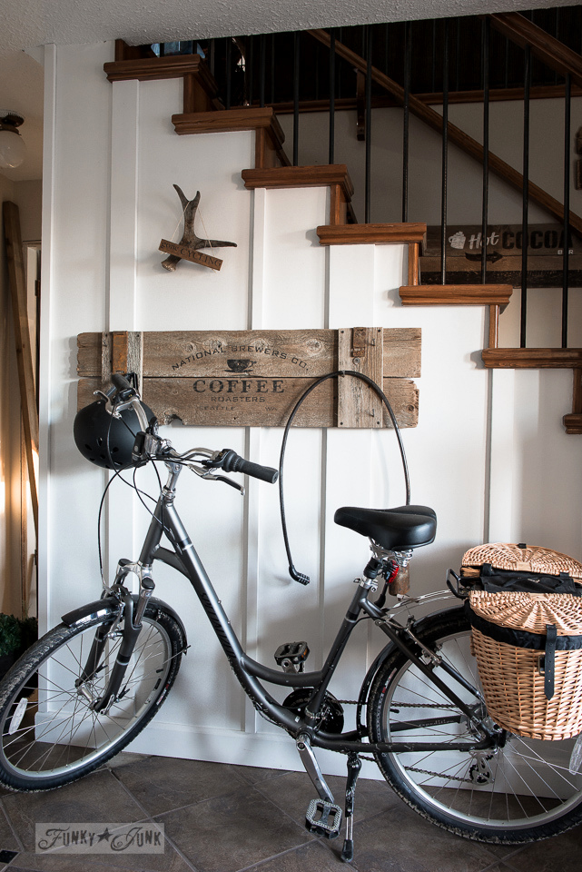 bike stored in a front entry with bike gear hanging on a white boarded wall and coffee sign / funkyjunkinteriors.net