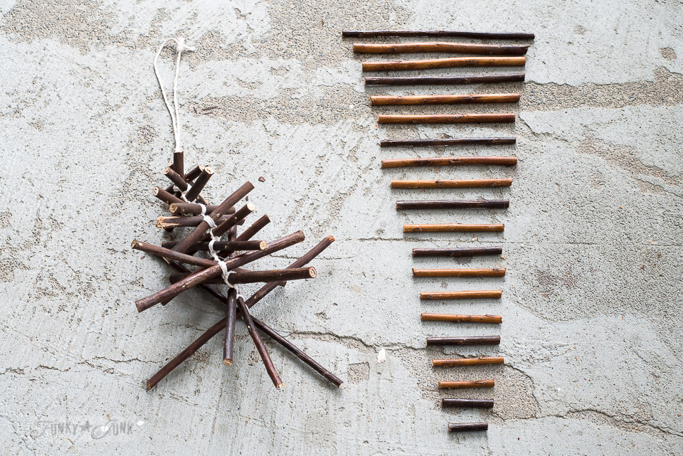 tieing the twigs / rustic twig Christmas tree ornament on a branch / funkyjunkinteriors.net