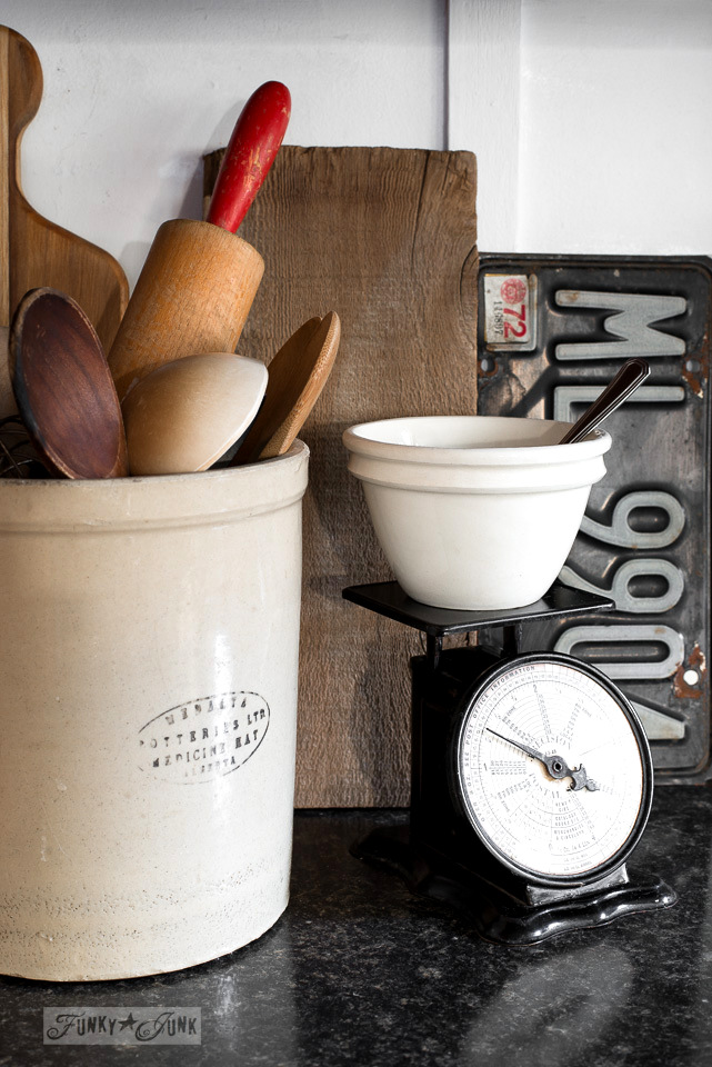 vintage crock pot holding wooden spoons and a vintage black scale in a rustic kitchen / funkjunkinteriors.net