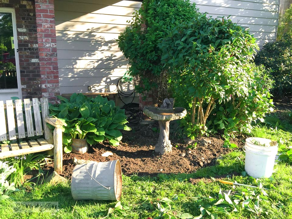 garden bed before with bare soil and empty bird bath