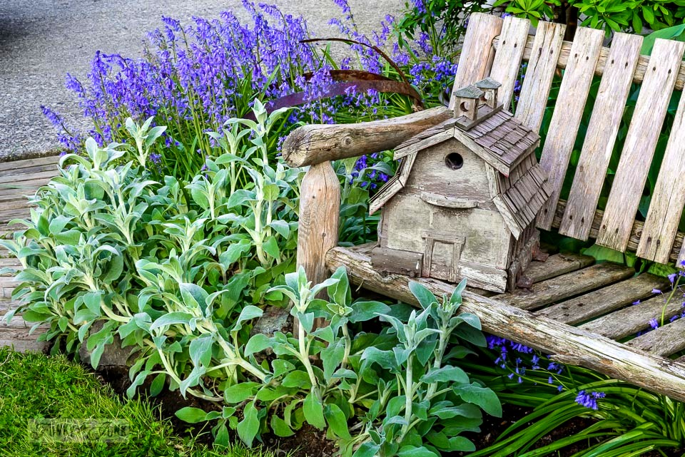 barn shaped birdhouse on a fence in a spring flowerbed / funkyjunkinteriors.net