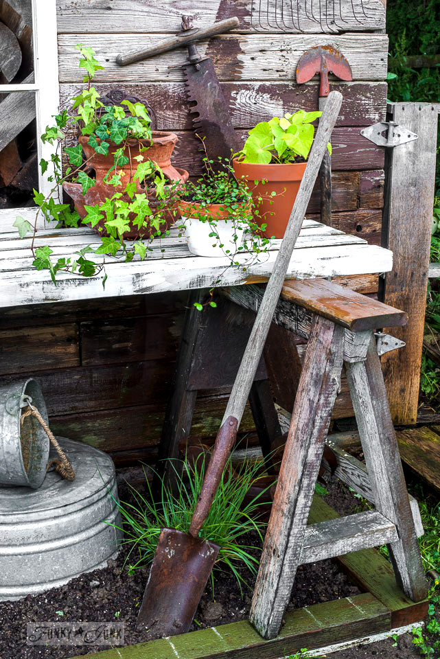 Potting bench made with sawhorses and planks against a rustic garden shed / funkyjunkinteriors.net