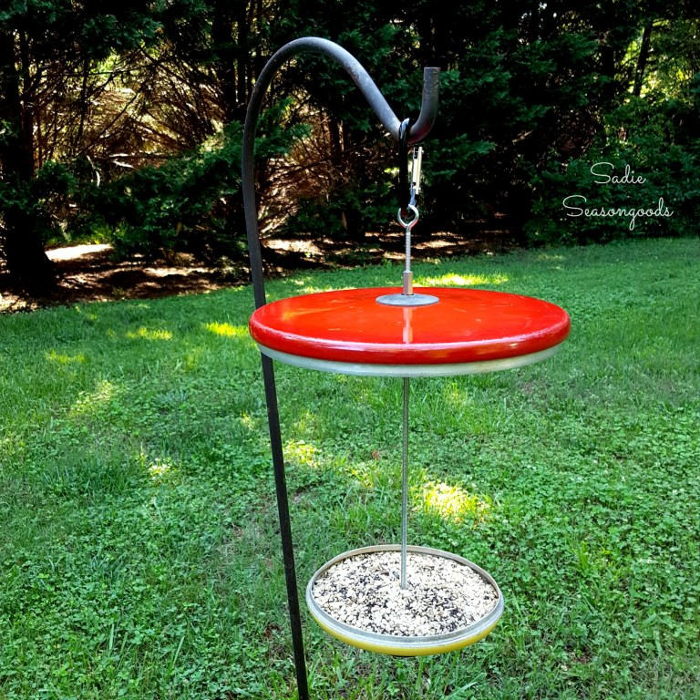 Pot lid bird feeder, by Sadie Seasongoods, featured on Funky Junk Interiors