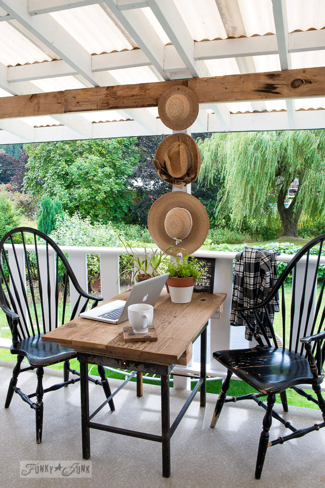 Patio sized reclaimed wood farm table for lap top use with straw hat wall art on a summer patio | funkyjunkinteriors.net