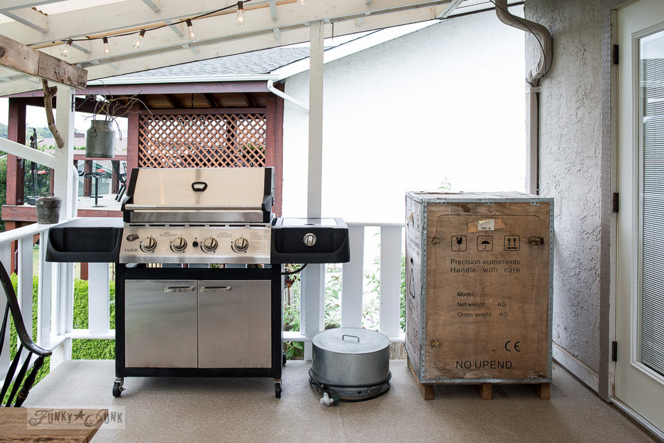 crate firewood storage cabinet and chrome and black grill on a summer patio | funkyjunkinteriors.net
