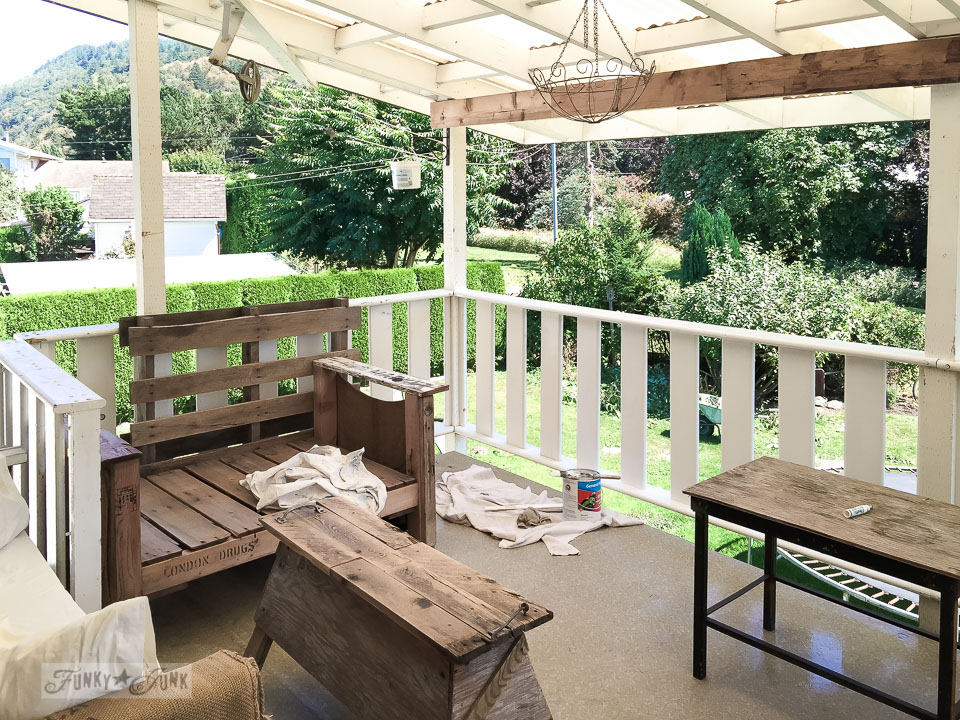 painting patio trim on a deck full of pallet wood furniture | funkyjunkinteriors.net
