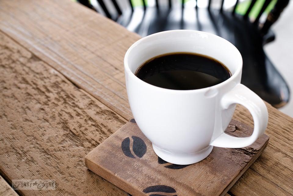 White mug of coffee on a rustic coffee bean stenciled wood coaster | funkyjunkinteriors.net