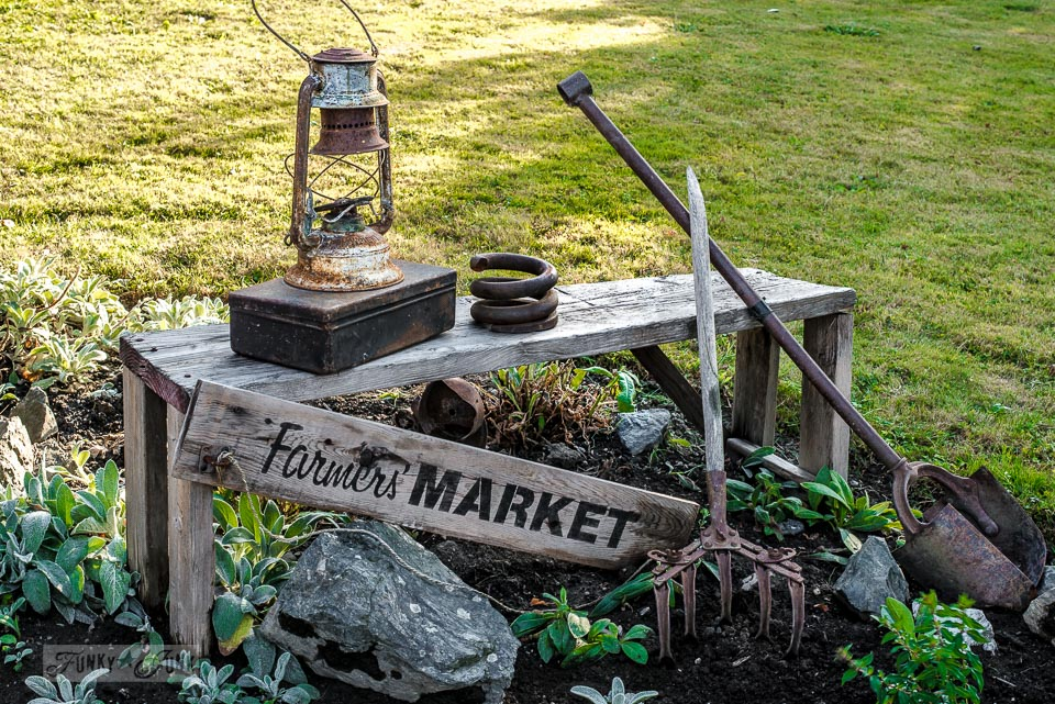 A freshly weeded Farmers' Market junk flower bed. Rusty lantern, spring, toolbox and tools as a flowerbed filler on funkyjunkinteriors.net