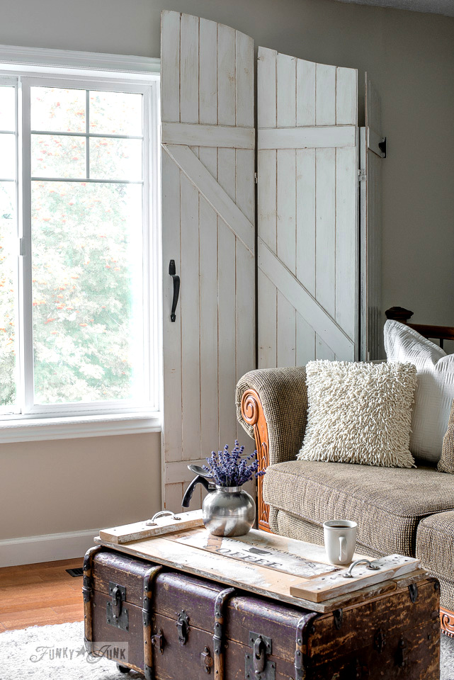 Rustic farmhouse living room with reclaimed wood trunk coffee table and old barn gate styled window treatement screens | funkyjunkinteriors.net
