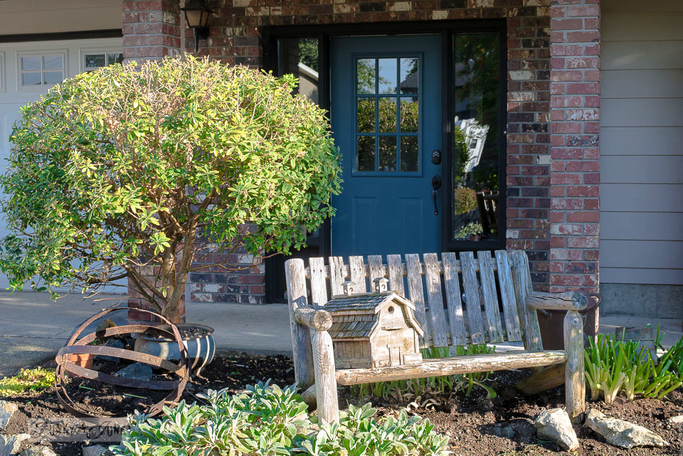 rustic garden bench with a birdhouse, garden orb and blue front door | funkyjunkinteriors.net