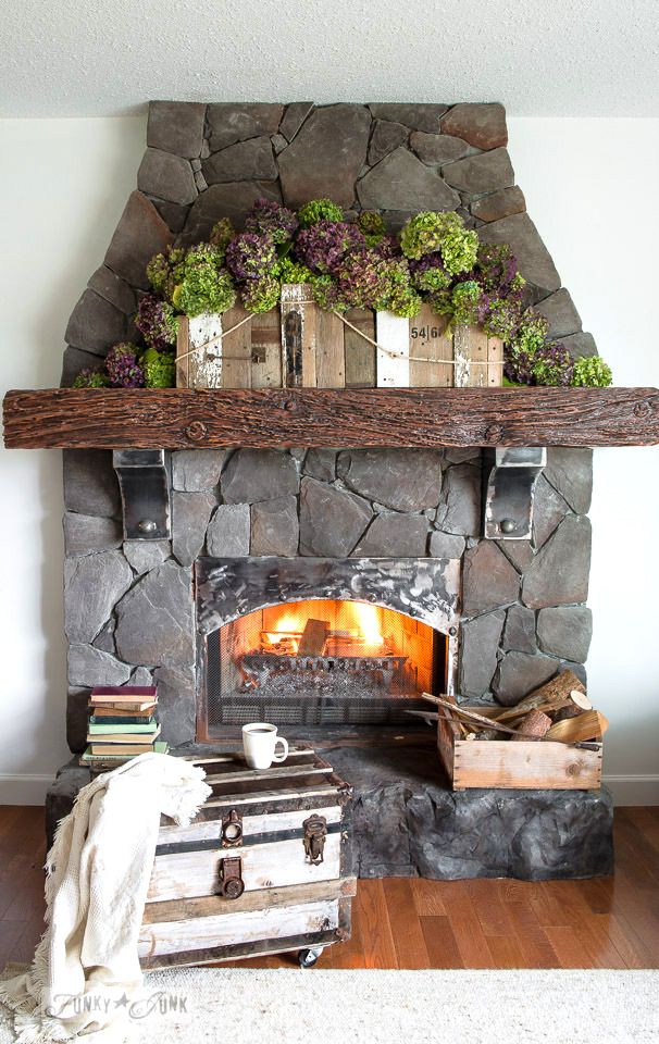 Stone fireplace makeover with metal corbels and beefy faux wood mantel