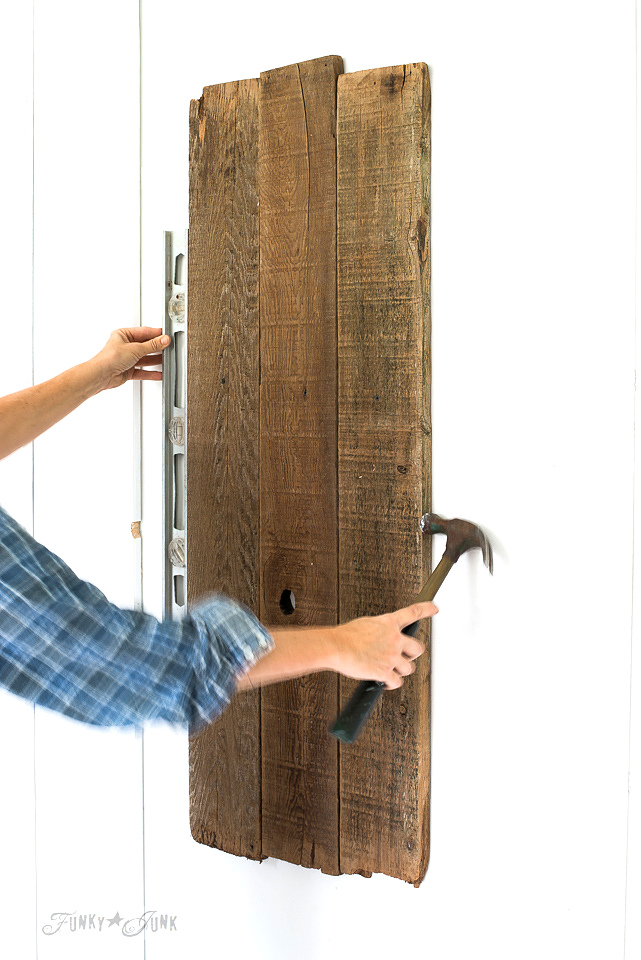 mounting the boards onto the wall with a level and hammer