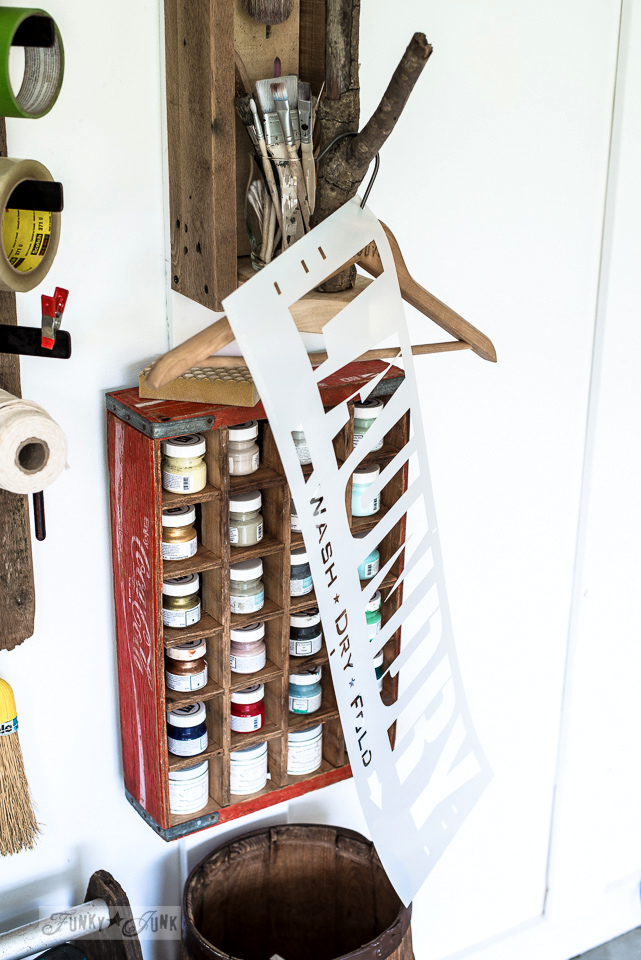 Coke crate paint storage, and branch handle for stencil hanging, part of a tool junk work station | funkyjunkinteriors.net
