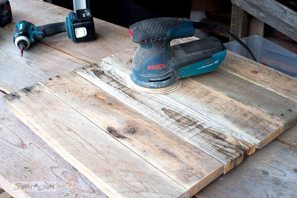Sanding pallet wood with a Bosch palm sander to make a rustic topped TV tray | funkyjunkinteriors.net