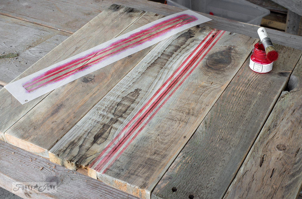Stencilling red grain sack lines onto a crate styled Christmas themed hot cocoa TV tray, from pallet wood and Funky Junk's Old Sign Stencils | funkyjunkinteriors.net