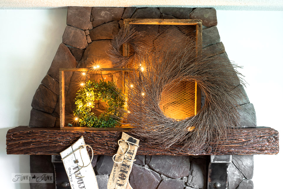 Old sign styled reclaimed wood Christmas stockings on a wreath filled fireplace using Funky Junk's Old Sign Stencils | funkyjunkinteriors.net