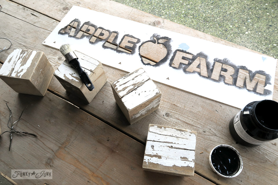 Stenciling FARM and FALL onto wooden blocks for a reclaimed wood coat hook shelf with Funky Junk's Old Sign Stencil APPLE FARM | funkyjunkinteriors.net