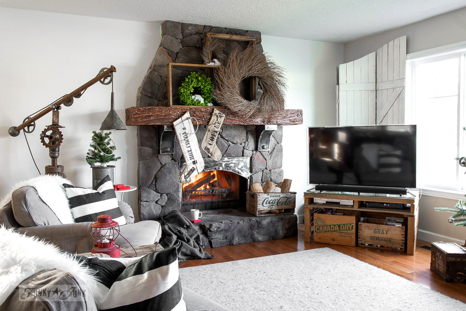 Christmas living room with wreath fireplace, wood stockings, rustic Christmas tree in a crate, junk lamp, and more. Take the tour! | funkyjunkinteriors.net