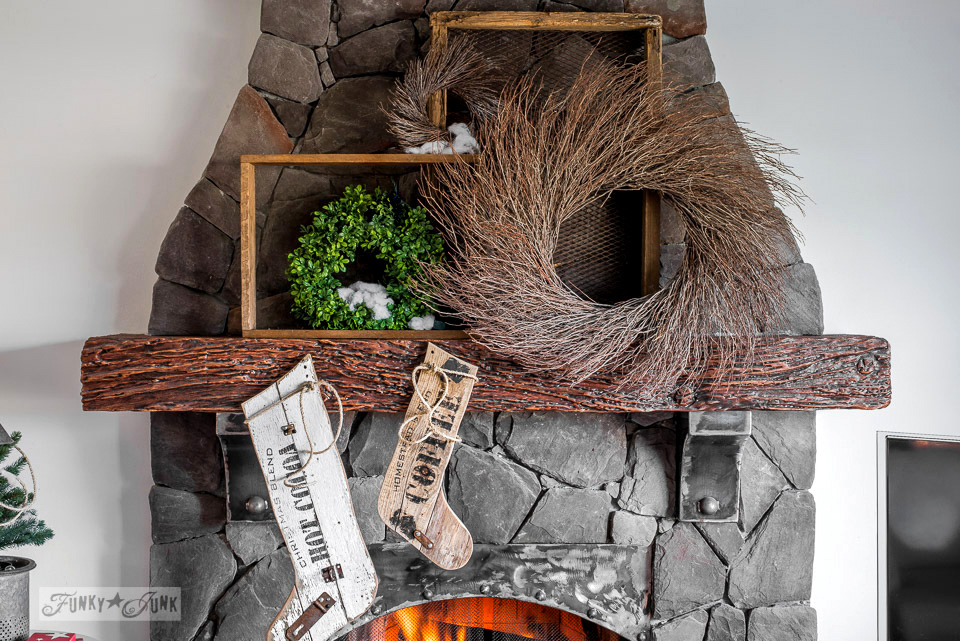 Wreath filled Christmas mantel on a rock fireplace, with reclaimed wood stockings, made with Funky Junk's Old Sign Stencils | funkyjunkinteriors.net