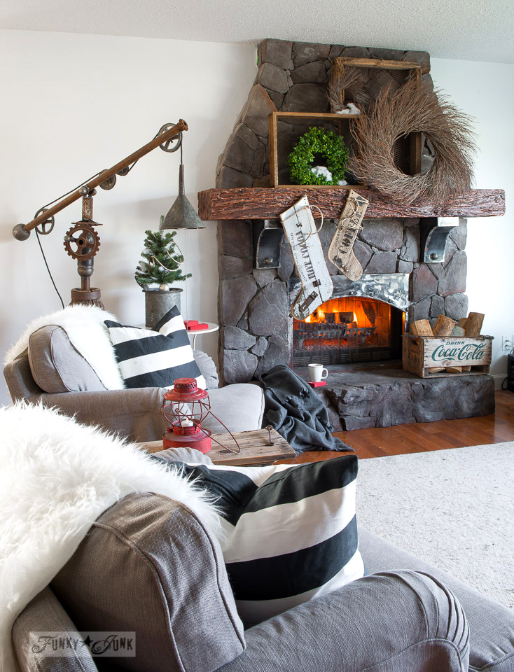 Wreath filled Christmas mantel on a rock fireplace, with reclaimed wood stockings, Ikea Stocksund chairs | funkyjunkinteriors.net