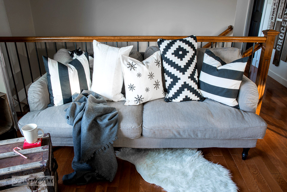 Black and white throw pillows on a Stocksund sofa, with stencilled black and white snowflake pilllow made with Funky Junk's Old Sign Stencils | funkyjunkinteriors.net