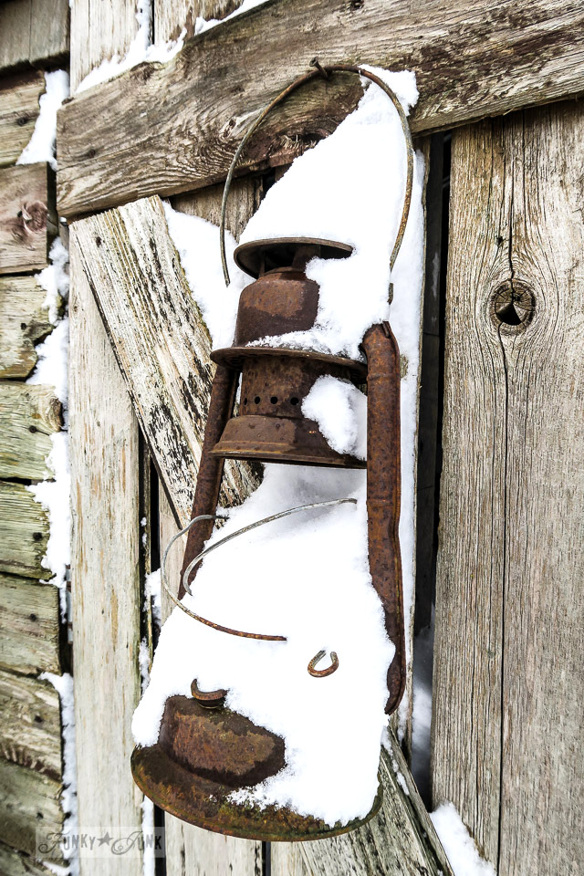 rusty lantern hanging from a rustic shed caught in the snow | funkyjunkinteriors.net