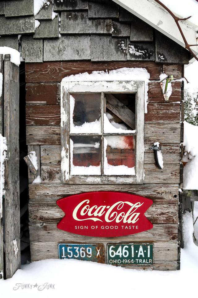 A rustic shed caught in the snow - with old barn window, fenceboards, and vintage signs and licence plates | funkyjunkinteriors.net