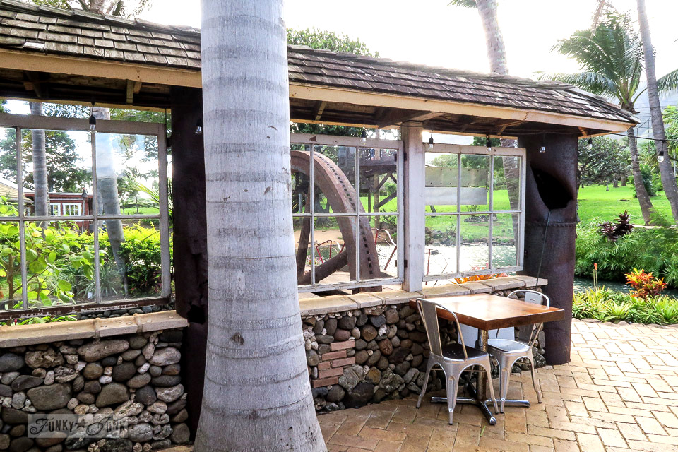 Casual outdoor dining beside lava rock walls and repurposed windows at The Mill House in Maui. A dream restaurant for junkers, plus, located at The Maui Tropical Plantation. | funkyjunkinteriors.net