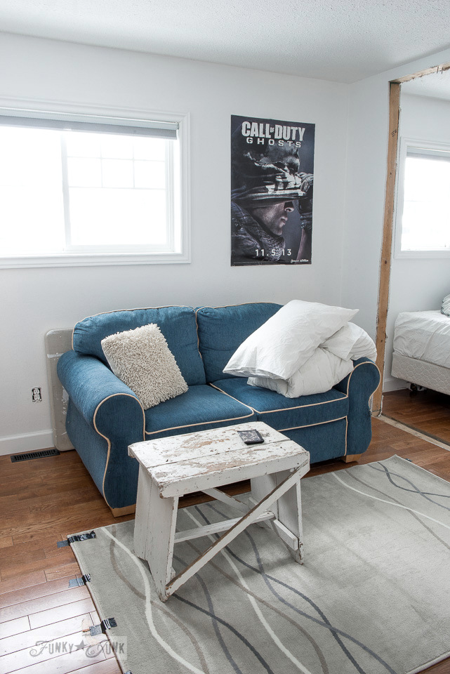 white walls with blue love seat in a teen's bedroom