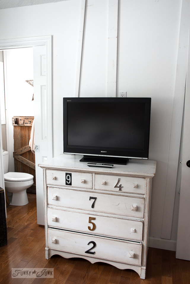 Tired white room, with board and batten trim and tv on numbered dresser