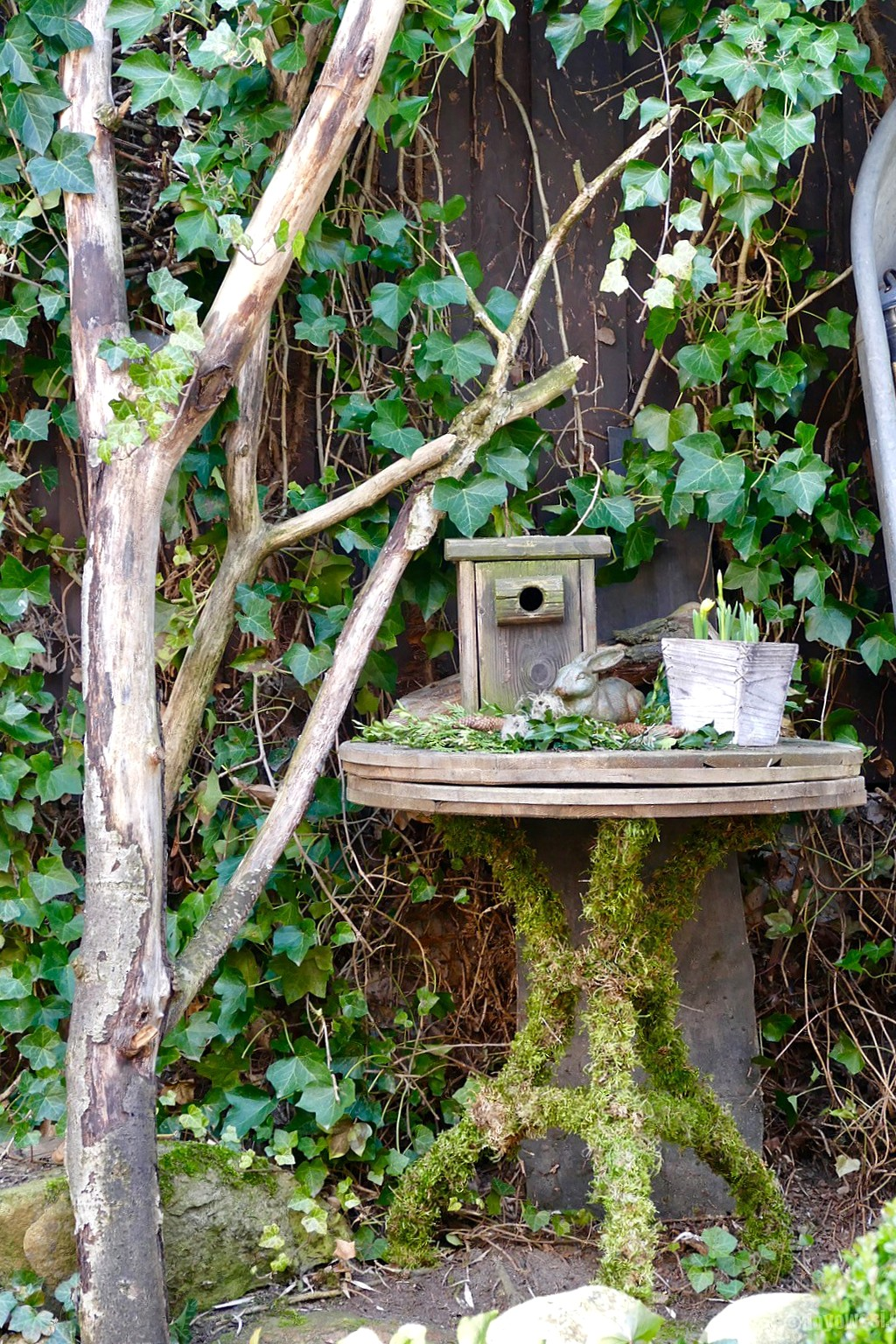 Moss covered wooden spool outdoor garden table, by Karin Urban - Natural Style, featured on Funky Junk Interiors using Funky Junk's Old Sign Stencils