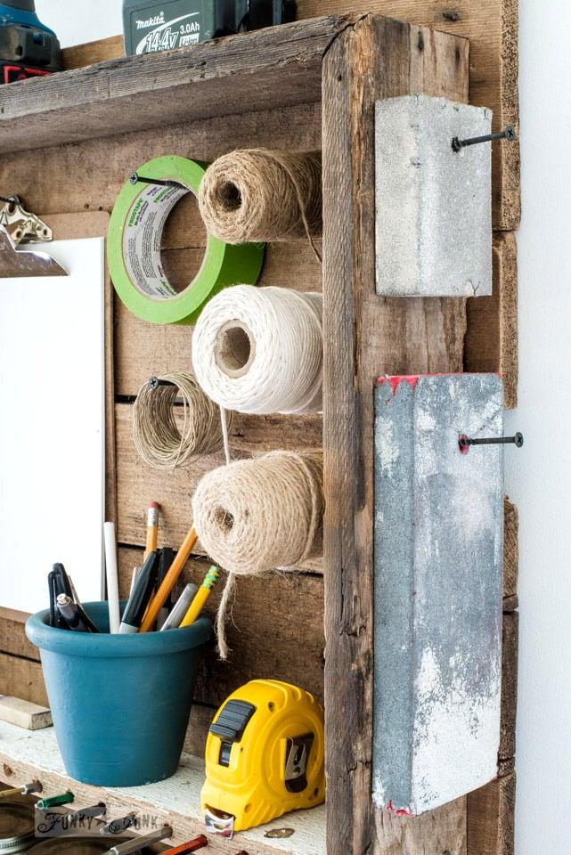 Twine and sanding sponge storage on a mini tool station hung on a wall | funkyjunkinteriors.net