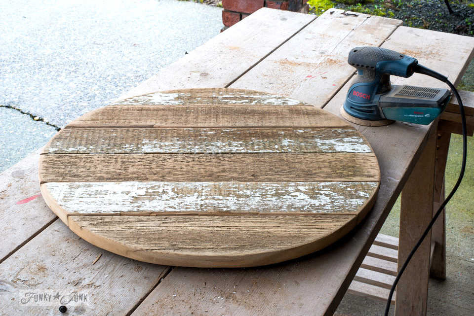 Using a Bosch palm sander to sand the face of a DIY reclaimed wood farmhouse clock | funkyjunkinteriors.net