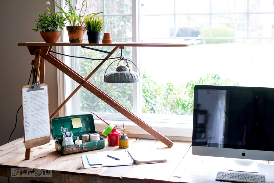 A vintage ironing board hooked up with a barn light becomes a cool farmhouse light for a rustic office desk!