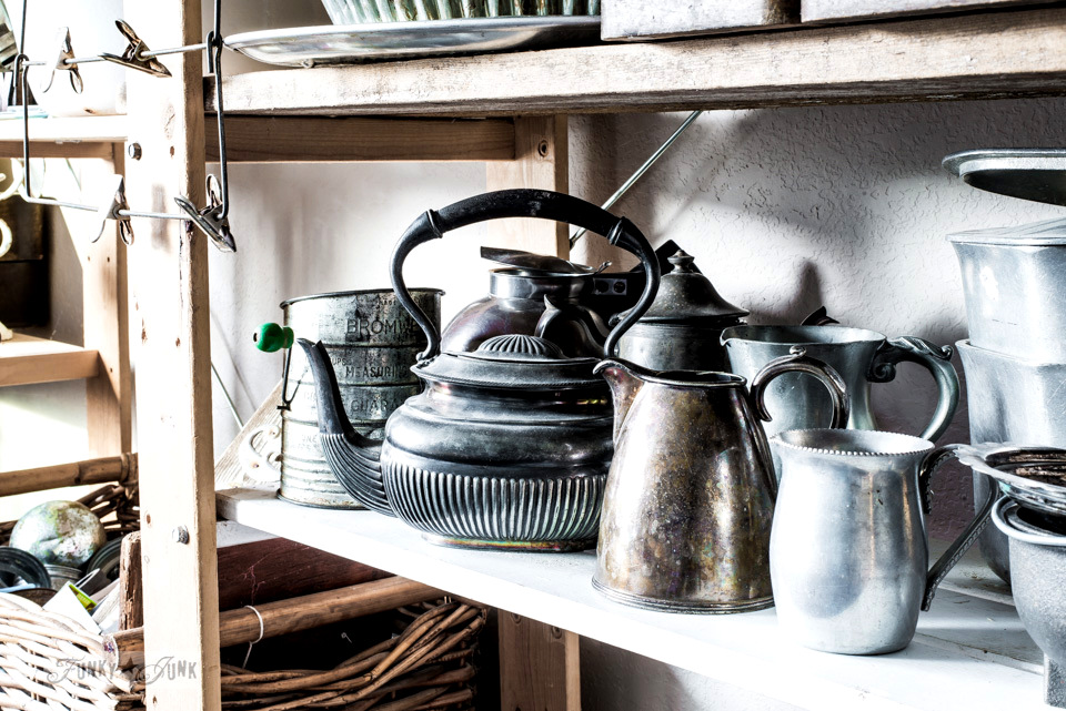A collection of silver tea kettles and creamers on a storage shelf full of staging components for decorating. funkyjunkinteriors.net