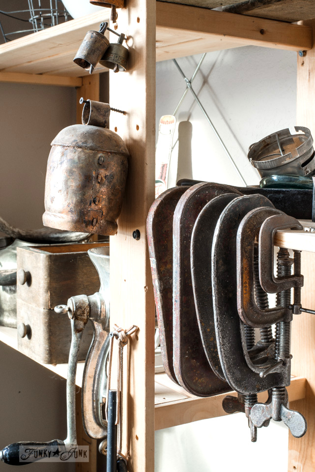 A collection of old bells and rusty metal clamps on a storage shelf full of staging components used for decorating. funkyjunkinteriors.net