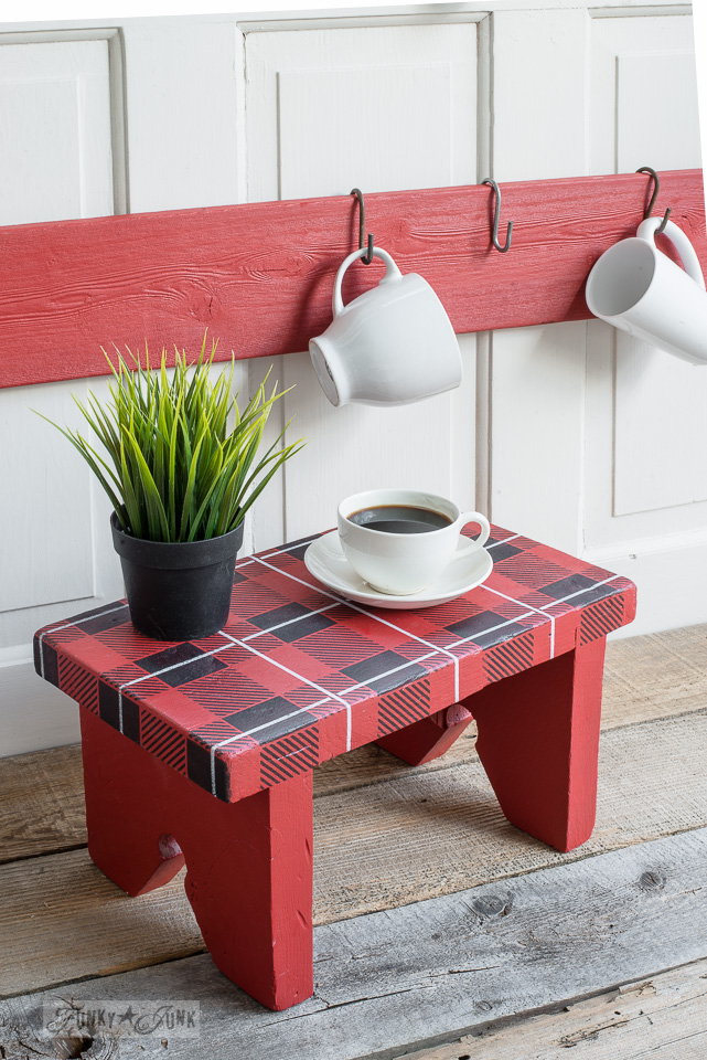 A vintage stool with a red and black Buffalo Check design with white plaid detail, made with Funky Junk's Old Sign Stencils